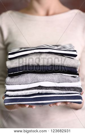 Woman holding washed and dried clothes on brick wall background