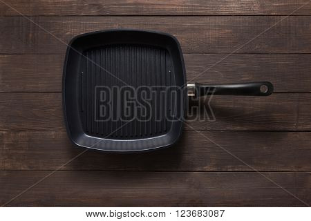 Cast iron griddle pan on wooden background.
