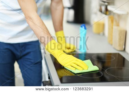 Man cleaning electric hob with spray and rag
