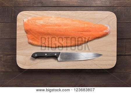 Fresh Salmon And Knife On Cutting Board On The Wooden Table. Top View