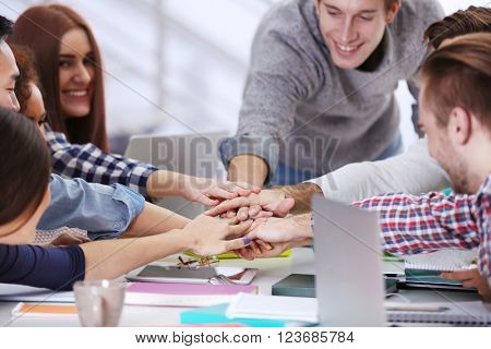 Young people putting hands together on the table at the office meeting