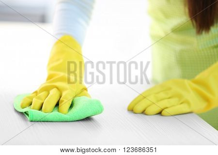 Woman in protective gloves cleaning kitchen table with rag
