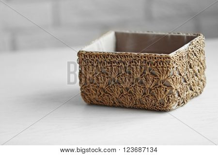 Wicker basket for home things on white table against wall background