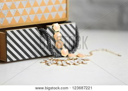Handmade chest of drawers for jewelry on wooden table background
