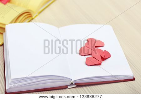 Book and heart shaped bookmarks on a  wooden background