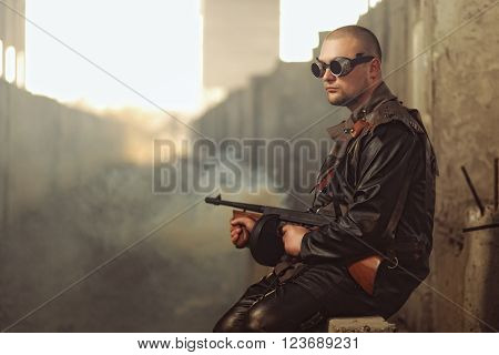 Portrait of a man from post-apocalyptic world with submachine gun and the black glasses in an abandoned building