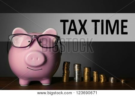 Tax Concept. Piggy bank with glasses and coins on table, gray background