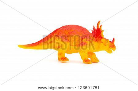 side view orange triceratops toy on a white background