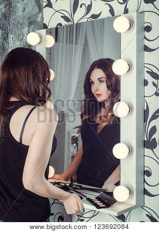 Young woman near mirror make makeup. Indoor shot.