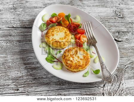 Potato patties and fresh tomato and celery salad on a light ceramic plate on wooden background.