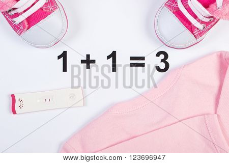 Pregnancy test with positive result and clothing for newborn baby shoes bodysuits concept of extending family and expecting for baby