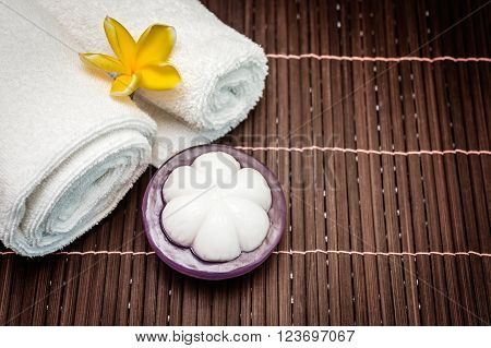 Spa soap mangosteen and towel on bamboo background. soft and fresh towels with flowers - beauty spa.