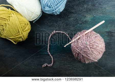 Balls of yarn with crochet hook on grey wooden table.
