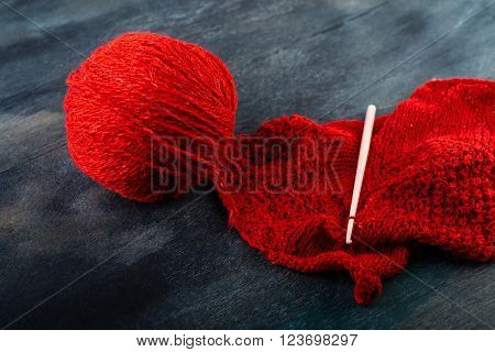 Crochet hook and red yarn ball on wooden background.