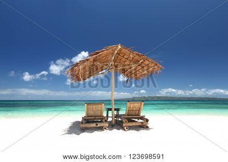 Relaxing couch chairs with straw parasol on white sandy beach at Philippines