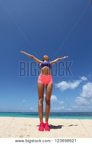 Beautiful young woman doing workout on tropical beach
