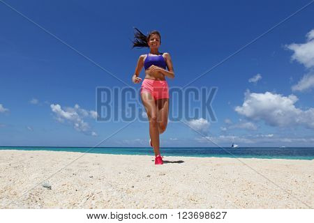 Running woman jogging on beach and sea on background