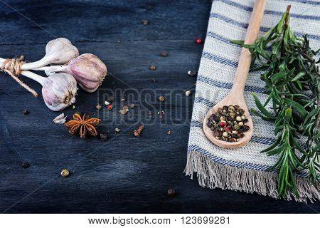 Fresh rosemary with garlic and peper on wooden background.