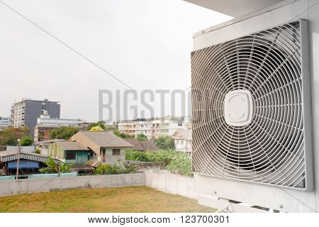 The air compressor with house and garden in background