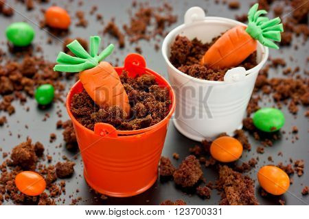 Easter food concept: desert in a decorative bucket chocolate crumb cream and sugar carrots. Treats for kids on Happy Easter holiday