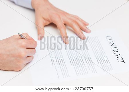 people, business and paperwork concept - close up of male hands signing contract document at office