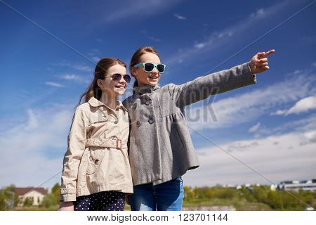people, children, friends and friendship concept -happy little girls in sunglasses hugging and pointing finger outdoors