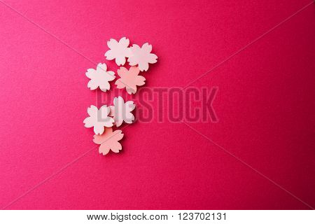 Cherry blossom background image. Cherry blossom pastel pink abstract background. Sakura or cherry flower shaped paper cutouts on soft pink background. Shallow depth of field.