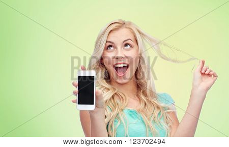emotions, expressions, technology and people concept - smiling young woman or teenage girl showing blank smartphone screen over green natural background