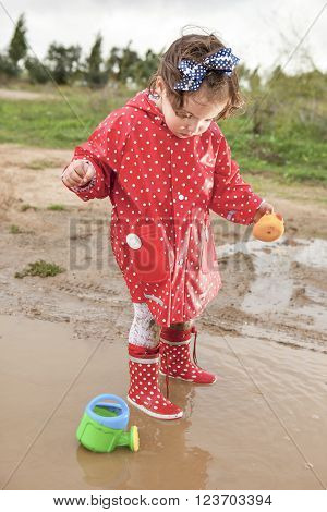 Baby girl dressed with dotted raincoat and rainboots playing with her sprinkling can