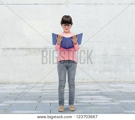 childhood, school, education, vision and people concept - happy little girl in eyeglasses reading book over urban city street background