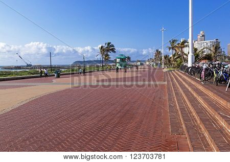 DURBAN SOUTH AFRICA - MARCH 23 2016: Many unknown people walk along paved promenade along Golden Mile beachfront in Durban South Africa