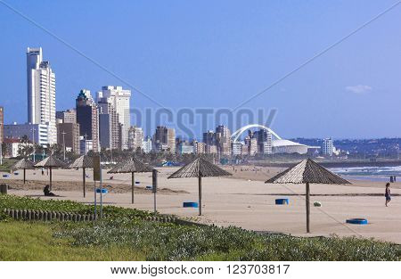 DURBAN SOUTH AFRICA - MARCH 23 2016: Many unknown people on early morning view of beach against city skyline in Durban South Africa