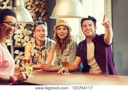 people, leisure, friendship and communication concept - group of happy smiling friends drinking beer and cocktails at bar or pub and pointing finger to something