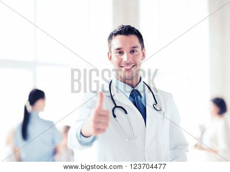 healthcare and medical concept - doctor with stethoscope showing thumbs up