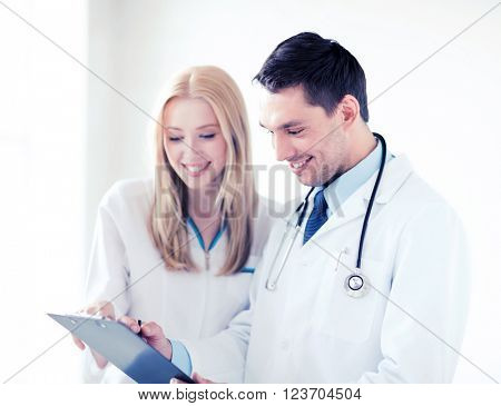 healthcare and medical concept - two doctors writing prescription