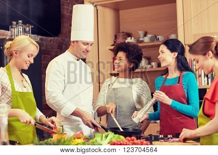 cooking class, culinary, food and people concept - happy group of women and male chef cook cooking in kitchen