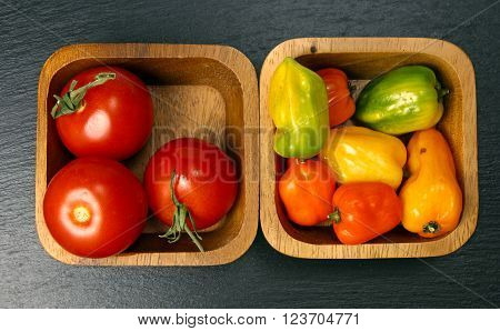 Overhead view of wooden bowls with cherry tomatoes and habanero peppers on a grey stone background with copy space.