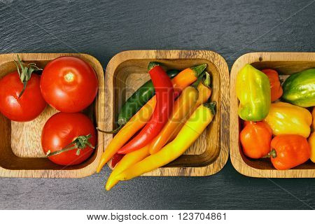 Overhead view of wooden bowls with cherry tomatoes colored peppers and habanero peppers on a grey stone background with copy space.