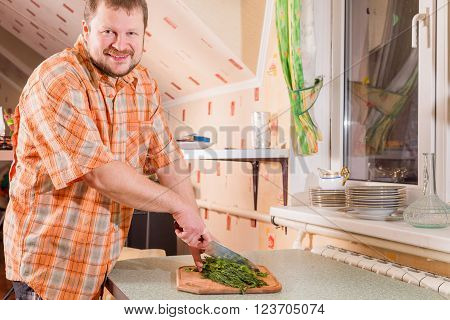 Adult man on kitchen cutting greenery by knife