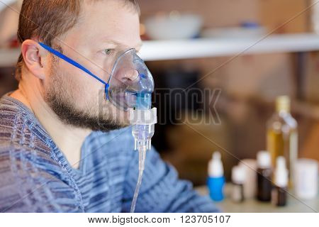 Man sitting with nebulizer mask close up view