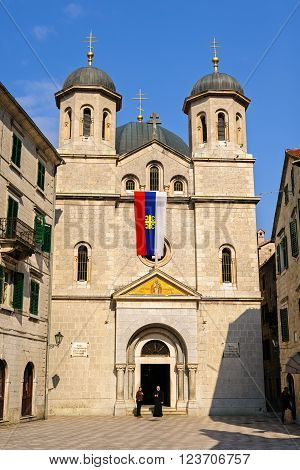 KOTOR/ MONTENEGRO - MARCH 12, 2015: View of Serbian Orthodox church of St. Nicholas with Serbian flag from St. Luke's Square