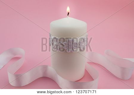 Close up photo of white candle lit isolated on pink background