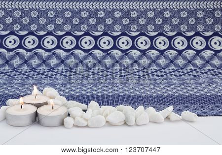 Candles, pebbles isolated on white and indigo cloth background