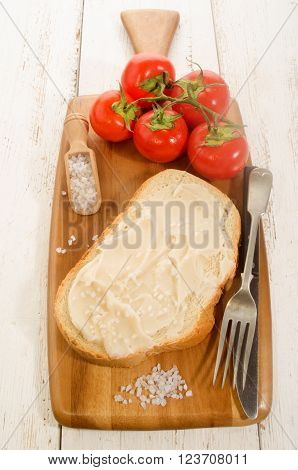 lard bread with coarse salt and tomatoes on wooden board