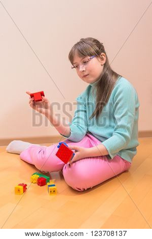 Young little girl sitting on floor playing toy modules