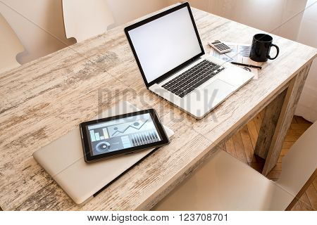 A wooden office Desktop with a Laptop and a Tablet PC.