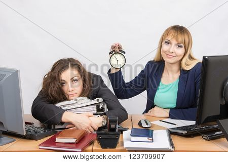 The Girl In The Office With A Smile Shows The Time On The Clock Next To The Exhausted Colleague