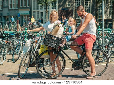 Young parents cycling with their little daughter at the streets of Amsterdam