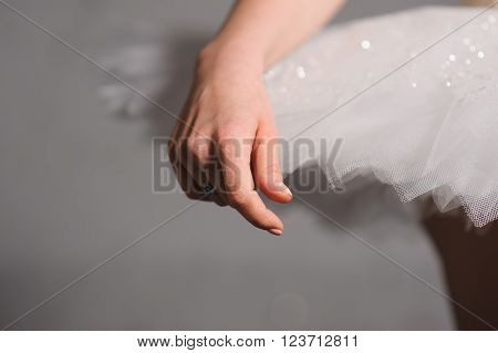 Close-up. hand ballerina on a background of white tutu. Graceful movements of hand. ballerina hand touched to the ballet skirt dress.