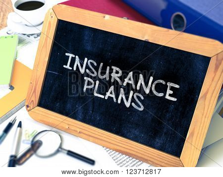 Insurance Plans Handwritten by White Chalk on a Blackboard. Composition with Small Chalkboard on Background of Working Table with Office Folders, Stationery, Reports. Blurred, Toned Image. 3D Render.